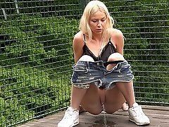 0  - Cute blonde in hotpants enjoys a long piss outside