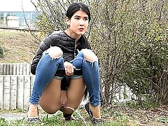0  - Pretty exotic girl pisses on the grass outside
